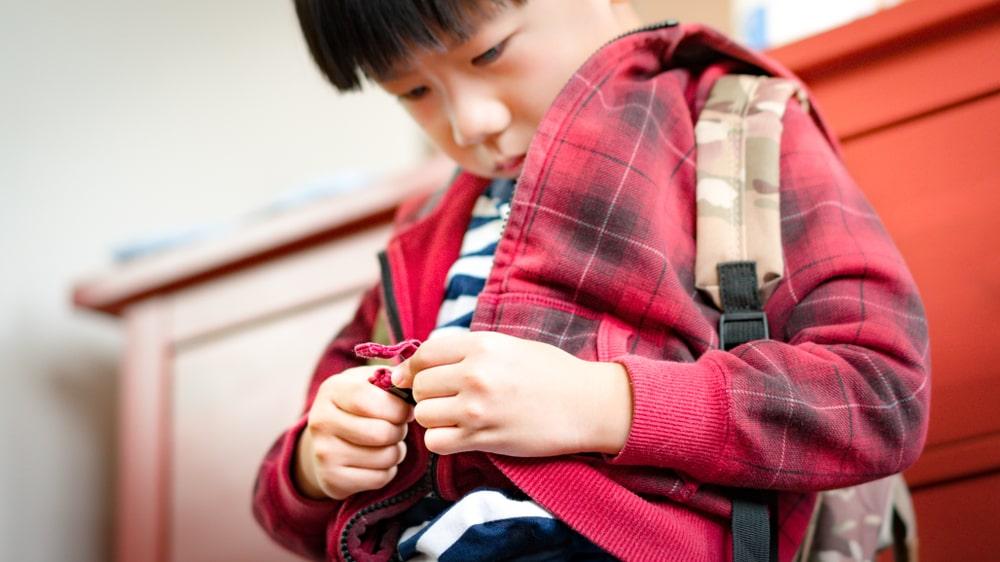 Un enfant développe son autonomie pour s'habiller