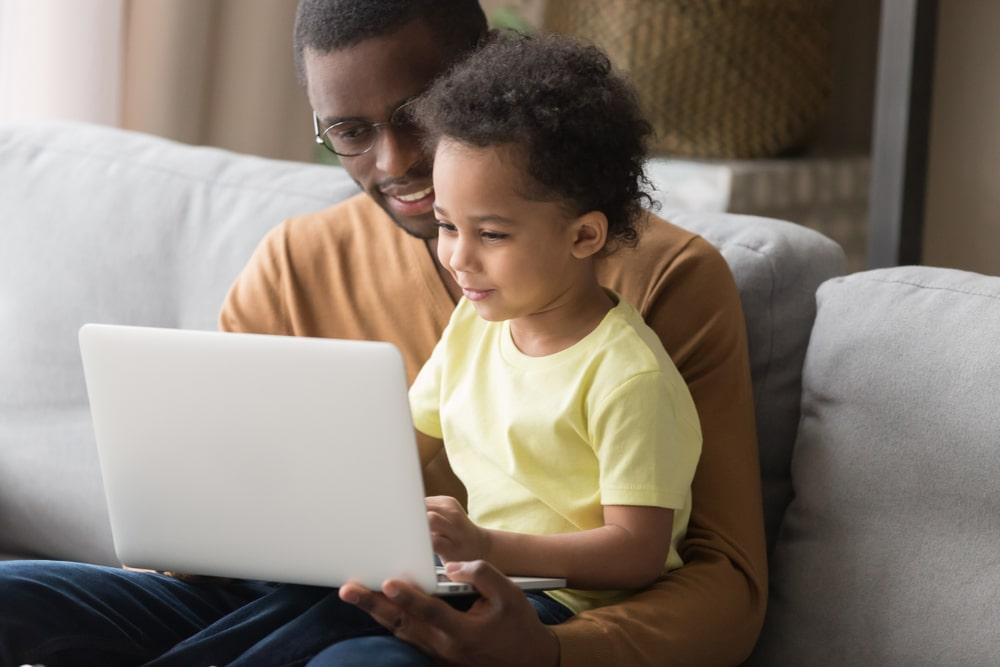 Un père et sa fille consulte des ressources éducatives